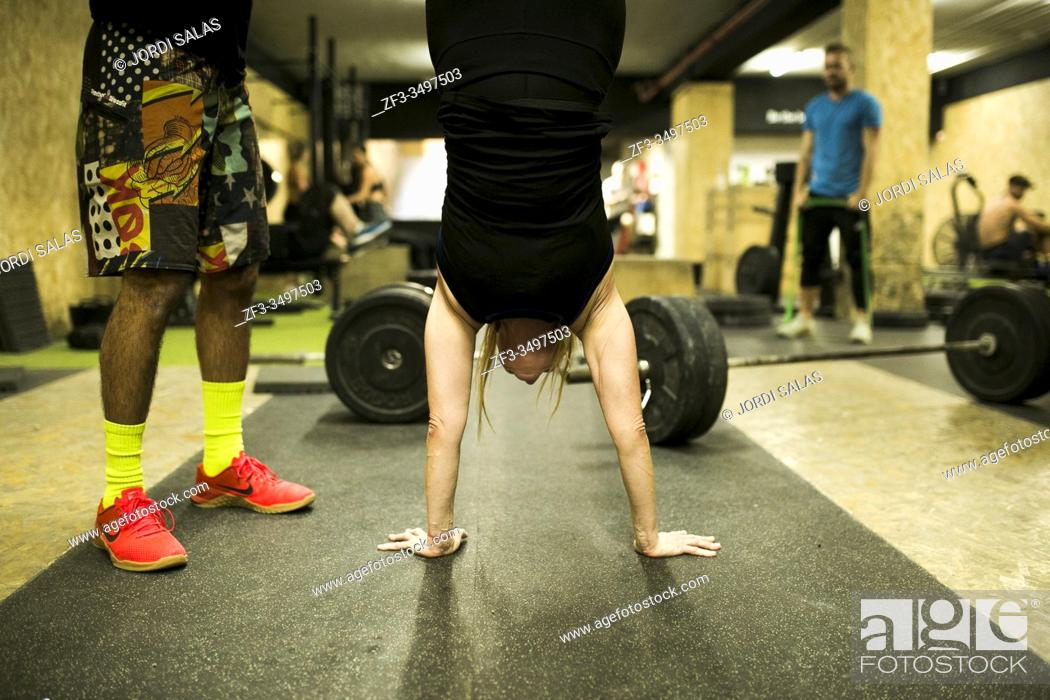 Stock Photo: Mid adult woman upside down in a gym.