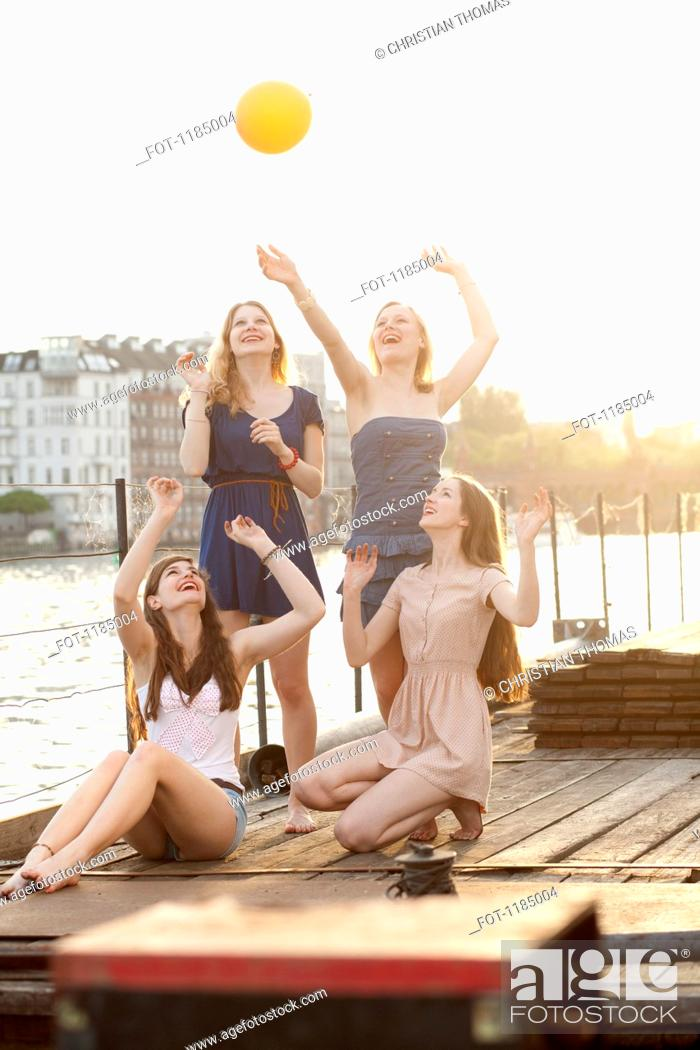Stock Photo: Four female friends tossing a ball around on a jetty next to Spree River, Berlin, Germany.