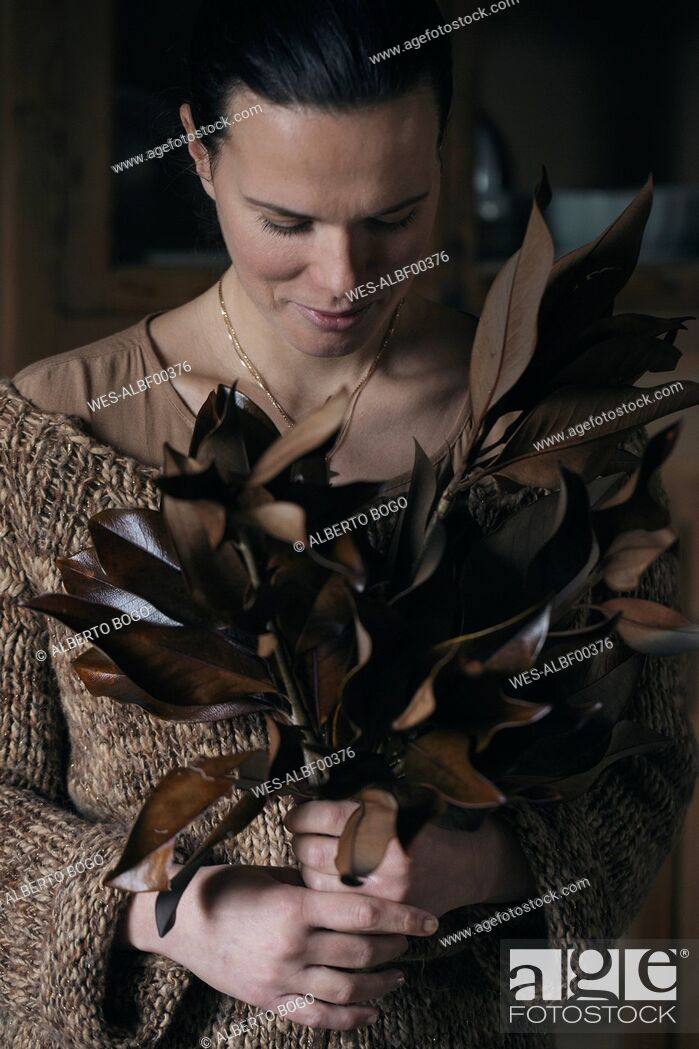 Stock Photo: Woman with bunch of twigs with brown leaves.