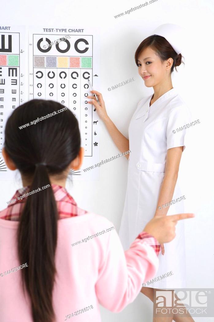 Stock Photo: Young nurse checking little girl's eye.