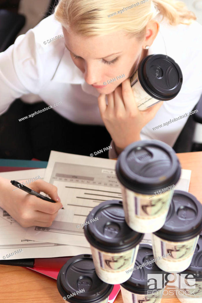 Stock Photo: Young girl in her 20's working with many cups of coffee to help her staying awake.