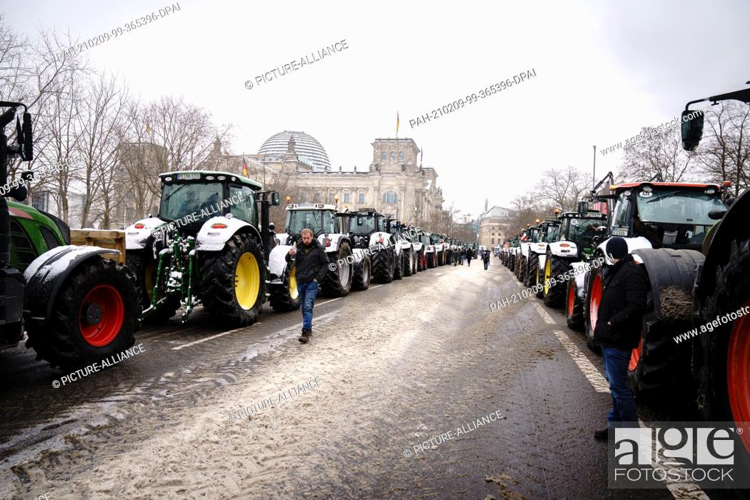 Stock Photo: 09 February 2021, Berlin: Tractors stand in front of the Reichstag building during a demonstration by farmers against the planned insect protection law.