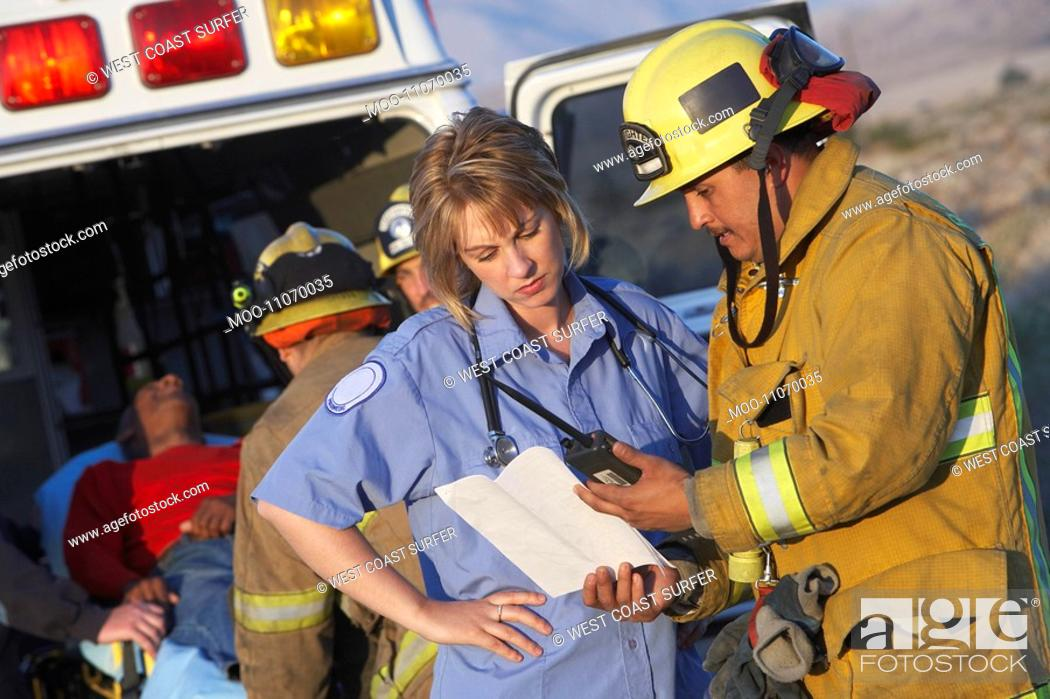 Stock Photo: Fire fighters and paramedics assisting injured man.