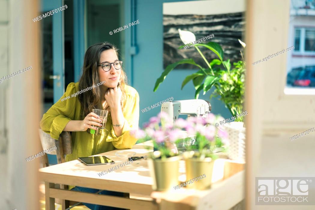 Stock Photo: Portrait of smiling fashion designer sitting at desk in her studio.