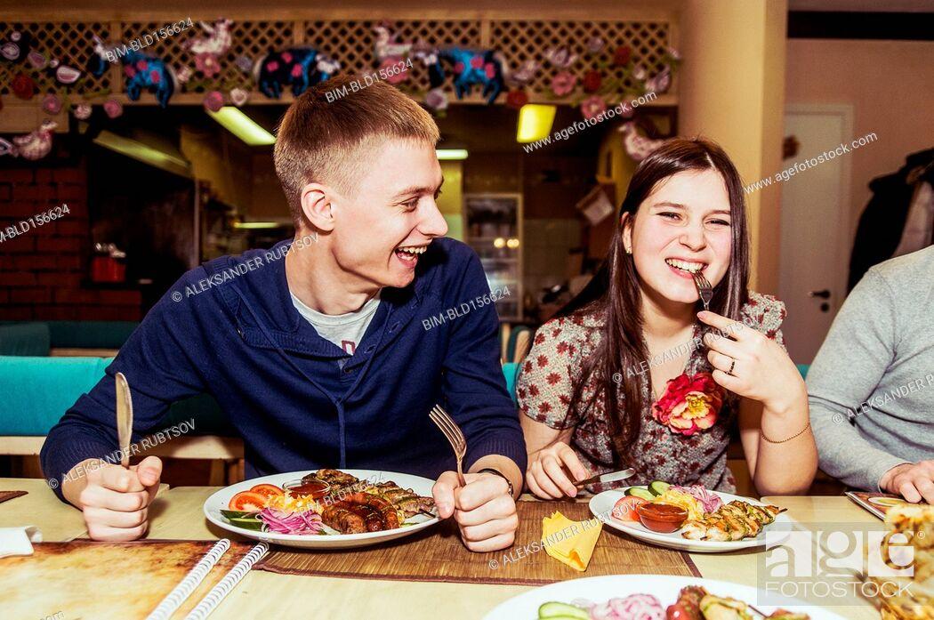 Stock Photo: Caucasian couple laughing in restaurant.