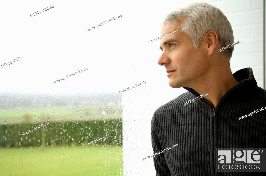 Imagen: Close-up of a mature man looking out through a window.