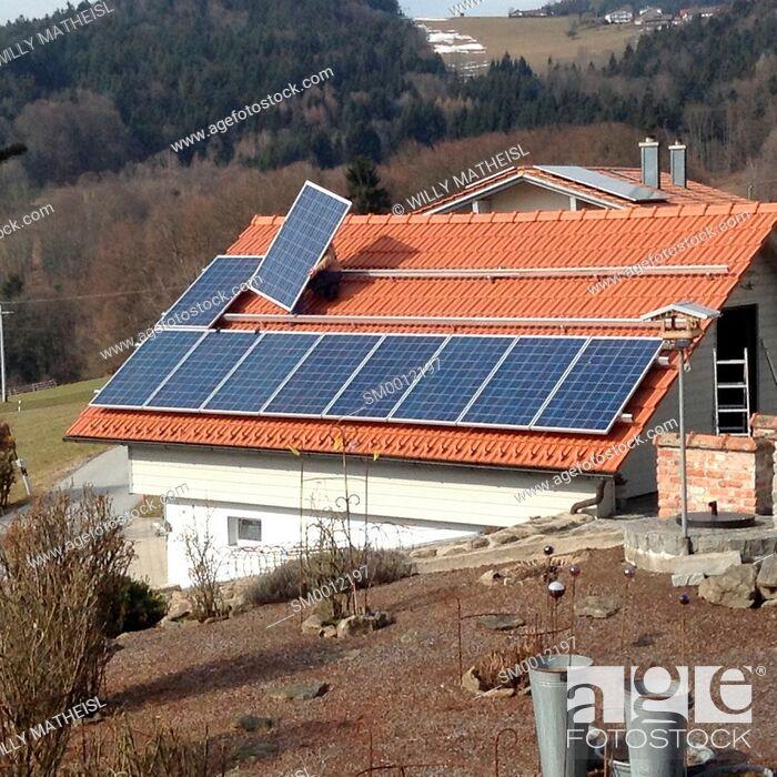 Stock Photo: worker installing solar panels on tiled roof, Bavaria, Germany, Europe.