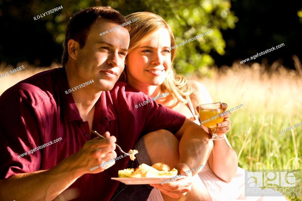 Stock Photo: A young couple sitting on the grass, having a picnic.
