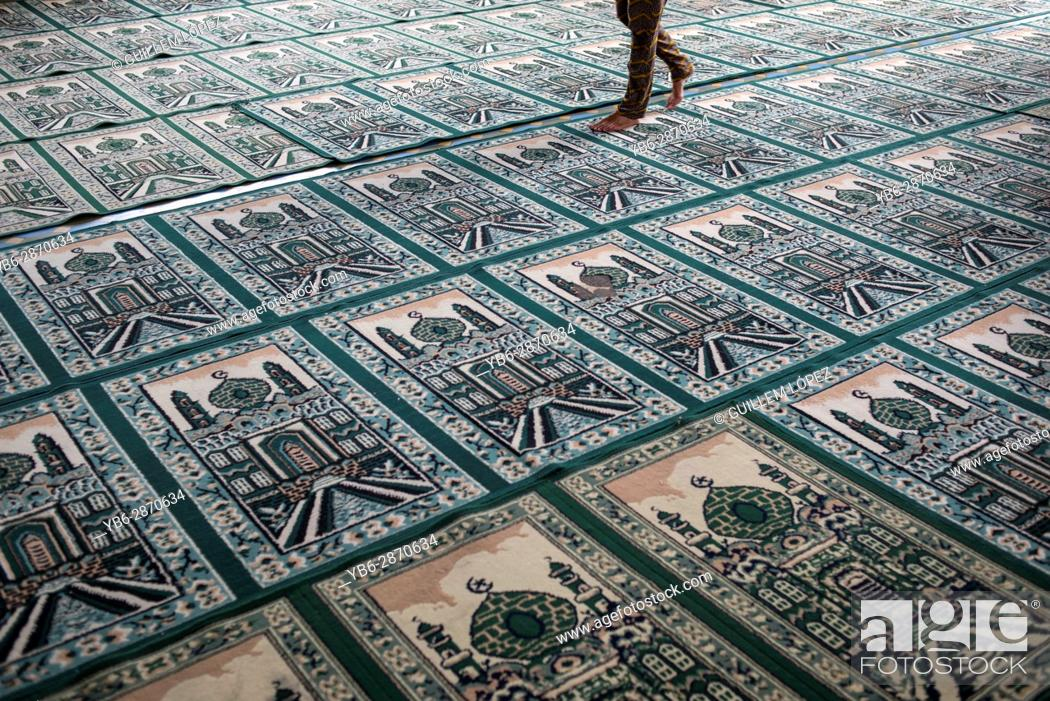 Stock Photo: A person walks on top of Muslim praying carpets inside the Grand Mosque in Medan, Sumatra, Indonesia.