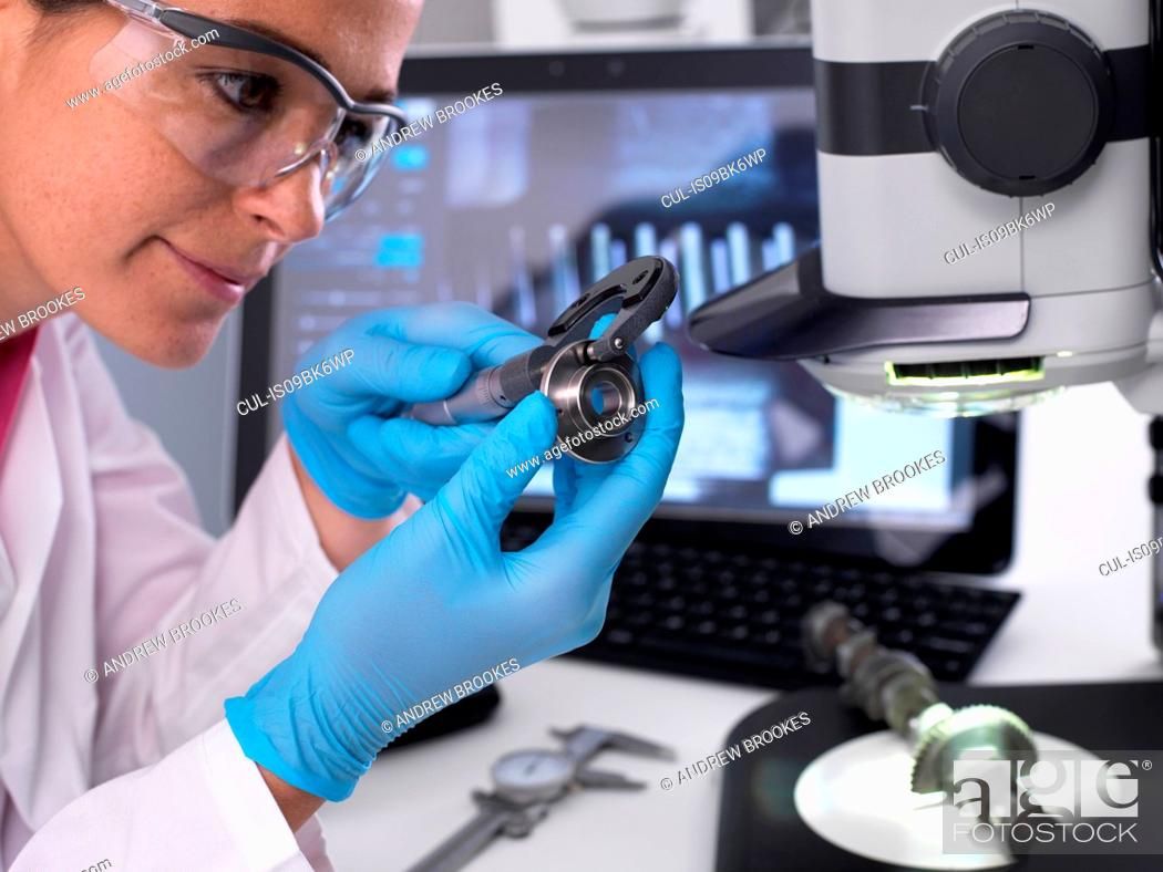 Stock Photo: Engineer measuring manufactured component for accuracy and quality control using a dial caliper, 3D stereo microscope in background.