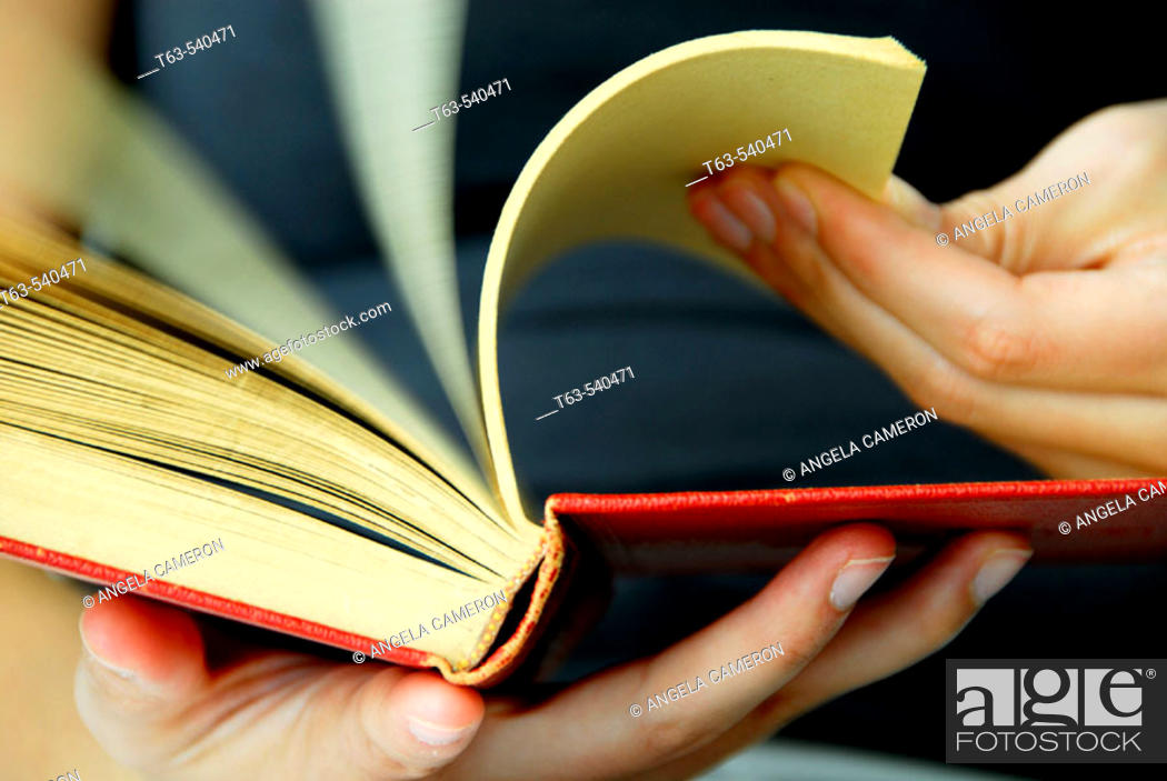 Stock Photo: 20 yr old woman flipping pages of a book.