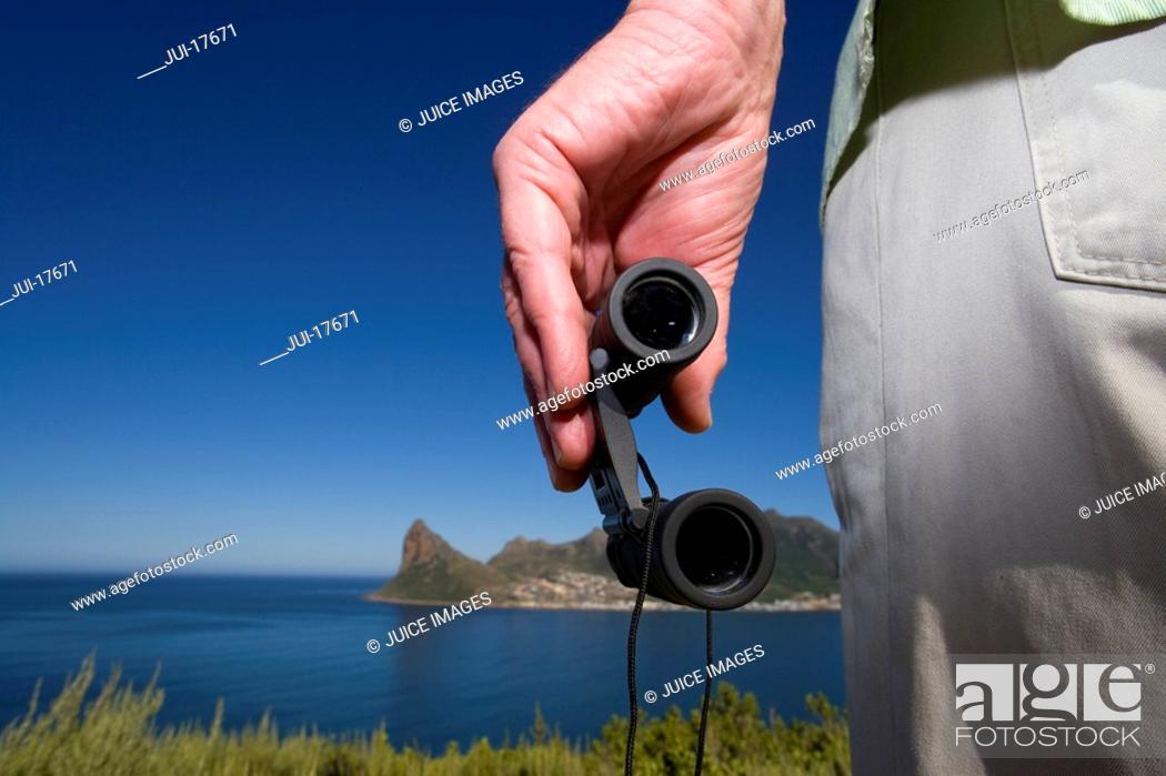 Stock Photo: Close up of man holding binoculars.