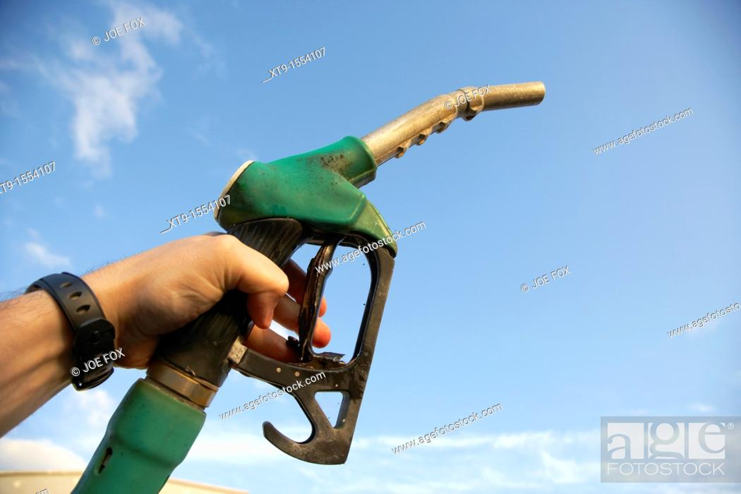 Stock Photo: mans hand holding unleaded petrol pump nozzle.
