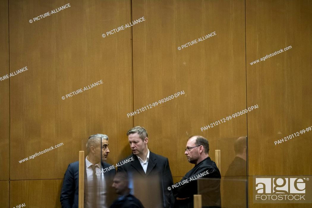Stock Photo: 12 January 2021, Hessen, Frankfurt/Main: The main defendant Stephan Ernst (M) speaks with his lawyers Mustafa Kaplan (l) and Jörg Hardies in a courtroom of the.