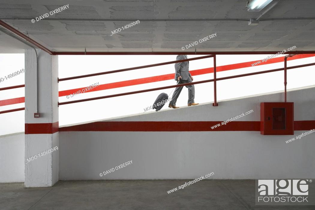 Stock Photo: Businessman walking up ramp in parking garage with luggage.