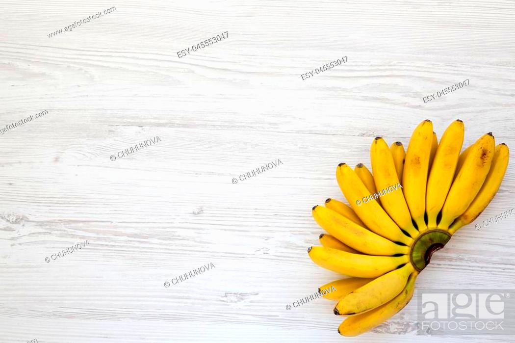 Stock Photo: Bunch of baby banana on white wooden background, top view. Space for text.