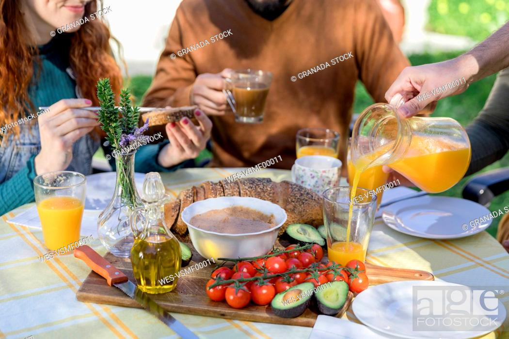 Stock Photo: Close-up of friends enjoying a healthy vegan breakfast outdoors.