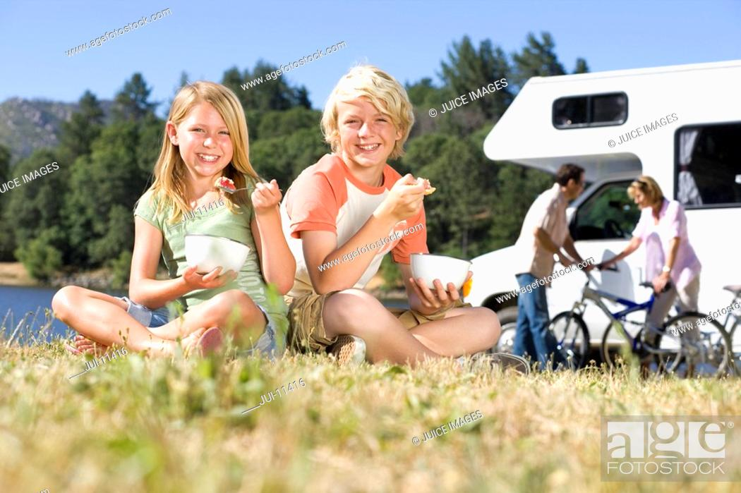 Stock Photo: Family of four by motor home, brother and sister 8-12 eating breakfast on grass, portrait.