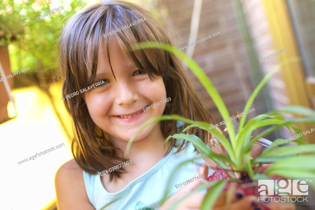 Stock Photo: Girl gardener transplanted a plant.