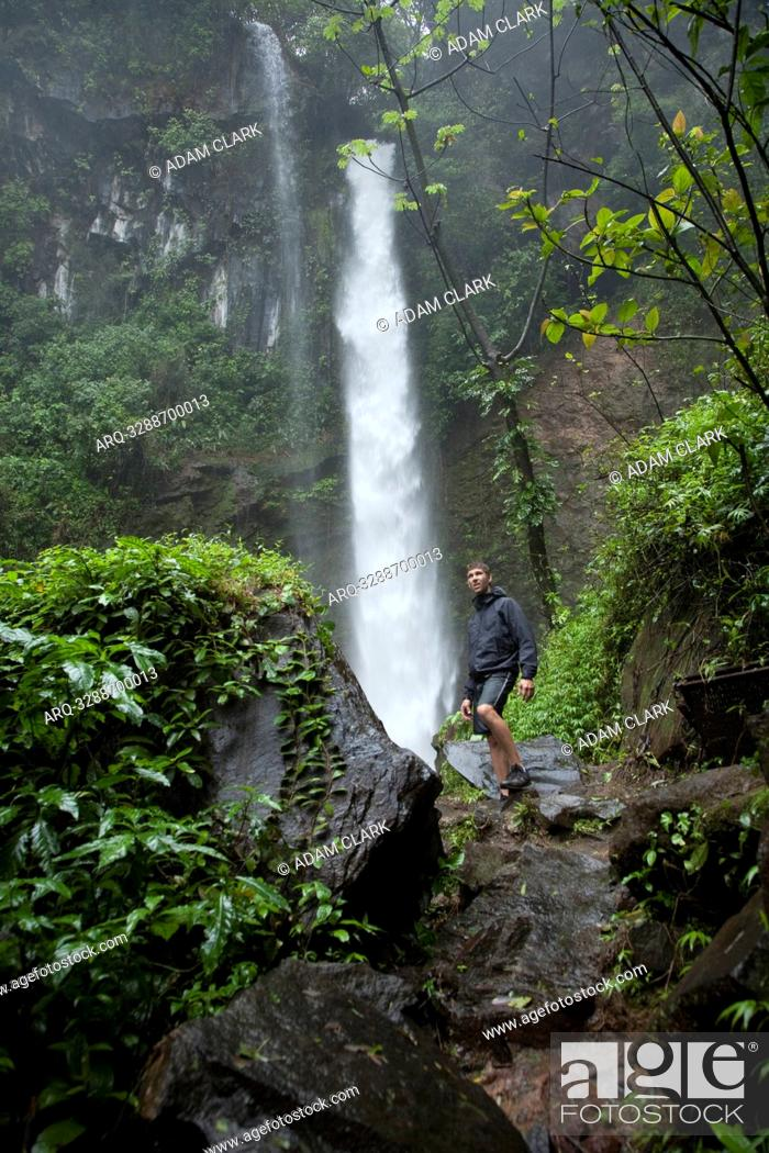 Stock Photo: A hiker under a jungle waterfall in Costa Rica.