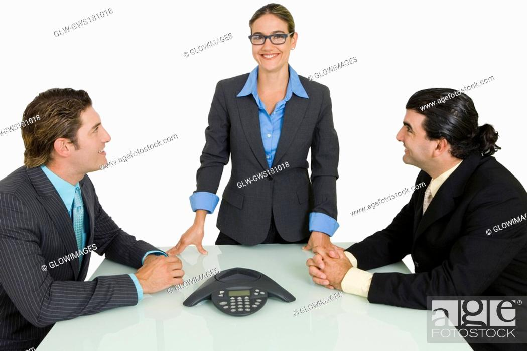 Stock Photo: Two businessmen and a businesswoman smiling in a board room.