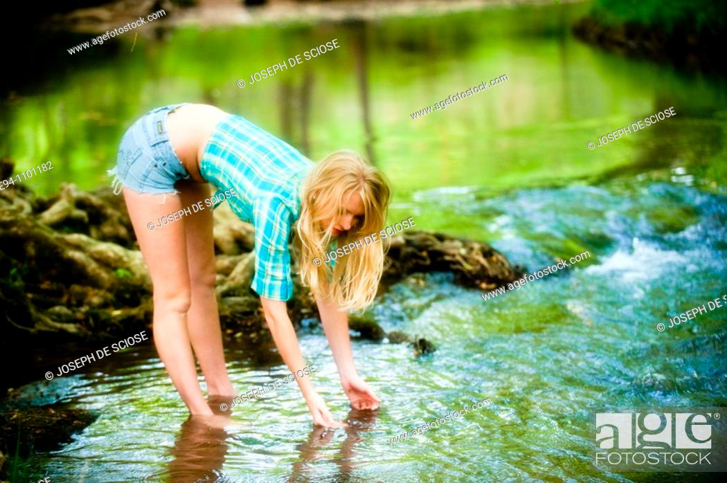 Stock Photo: Young blond woman, cut off shorts by a small river in a country outdoor setting.