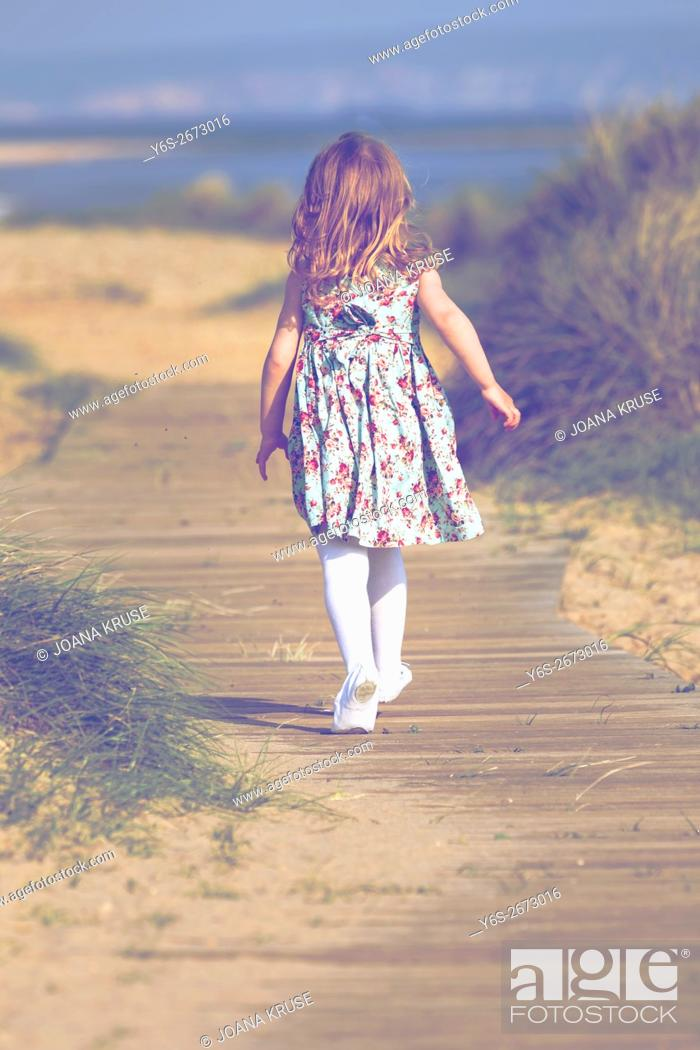 Photo de stock: a 3 year old girl running on a boardwalk at the beach.