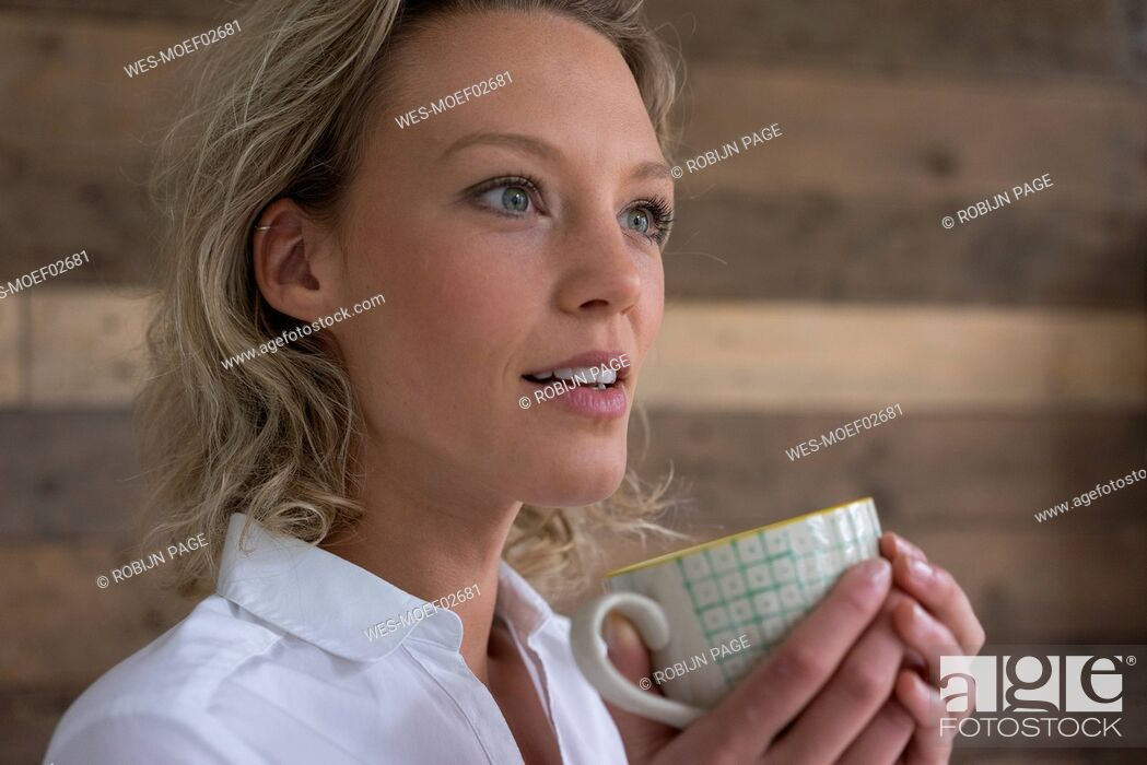 Stock Photo: Young businesswoman holding cup of coffee looking sideways.