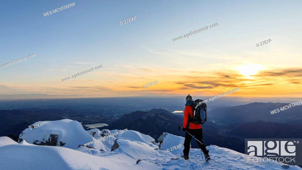 Stock Photo: Mountaineer walking on top of a snowy mountain, Lecco, Italy.