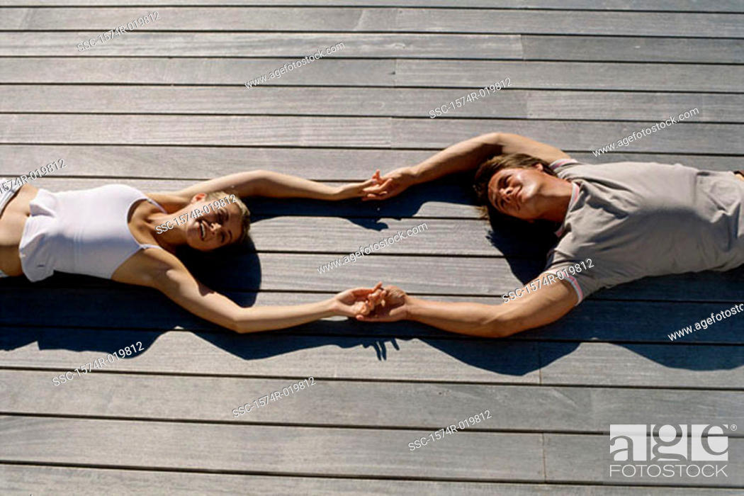 Stock Photo: High angle view of a young couple lying on wooden planks holding hands.