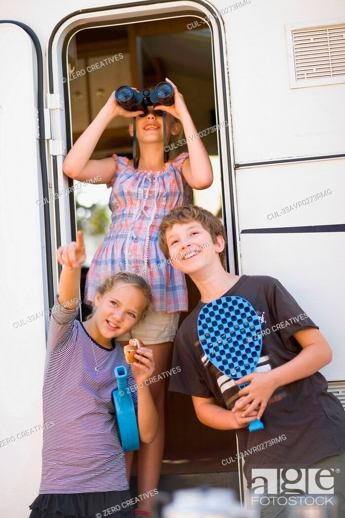 Photo de stock: Children using binoculars outside RV.