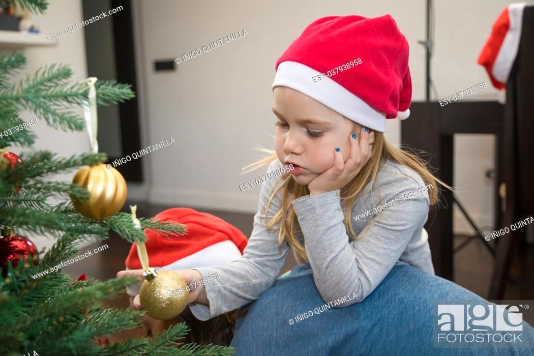 Stock Photo: funny scene: four years blonde cute girl with red Santa Claus hat, holding a golden ball in Christmas tree, resting on her mother back, at home.