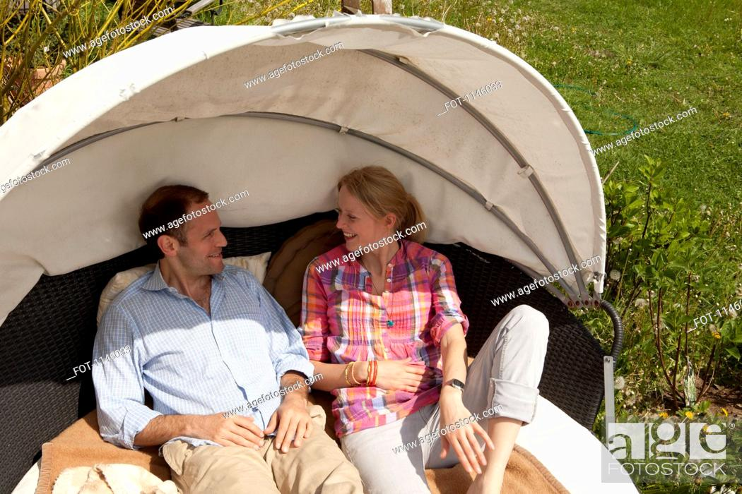Stock Photo: A couple reclining in a cabana in their backyard.