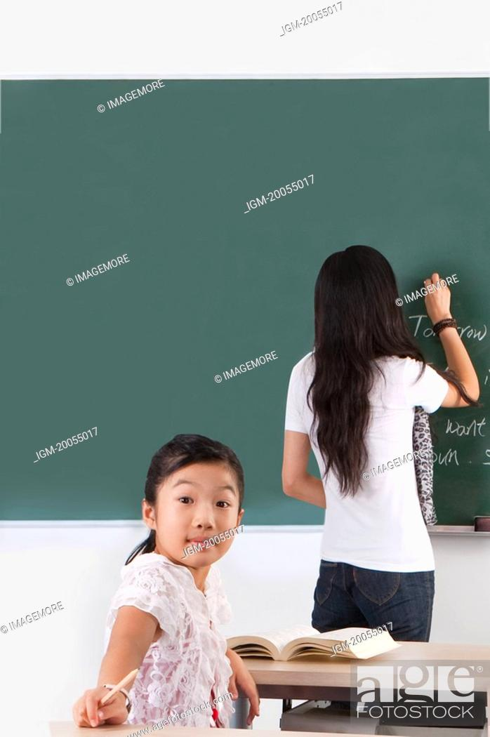 Stock Photo: Child, Girl looking over shoulder with teacher standing and writing.