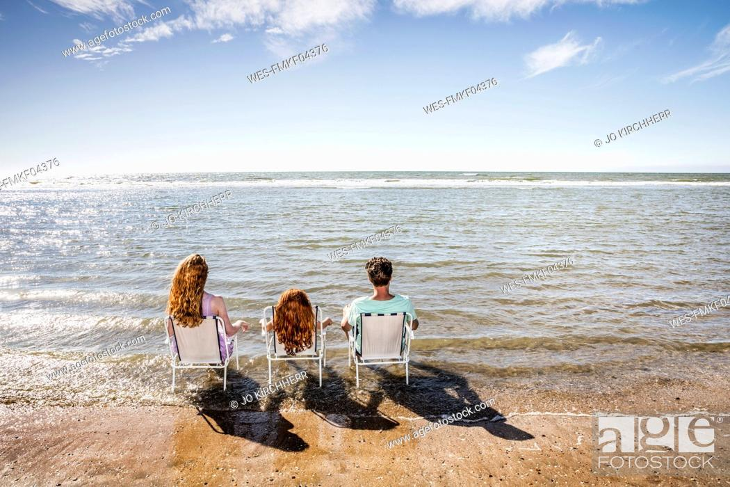 Photo de stock: Netherlands, Zandvoort, family sitting on chairs in the sea.
