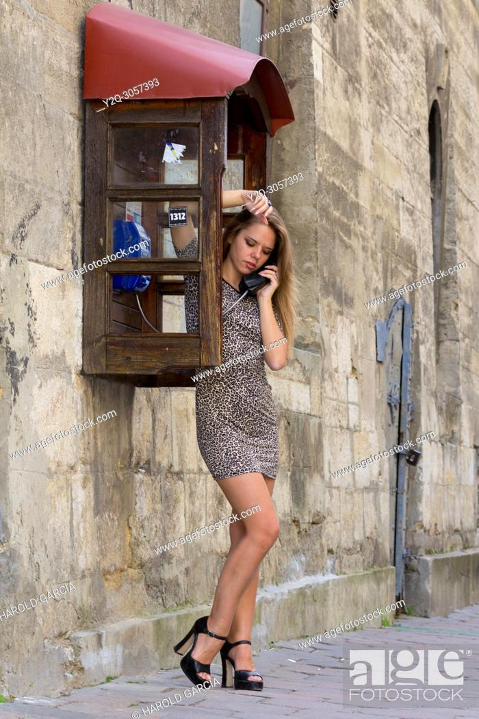 Imagen: Sexy and elegant Ukrainian woman wearing a leopard-skin print suit posing reclining to a telephone booth and talking on the phone for a photographic sequence in.