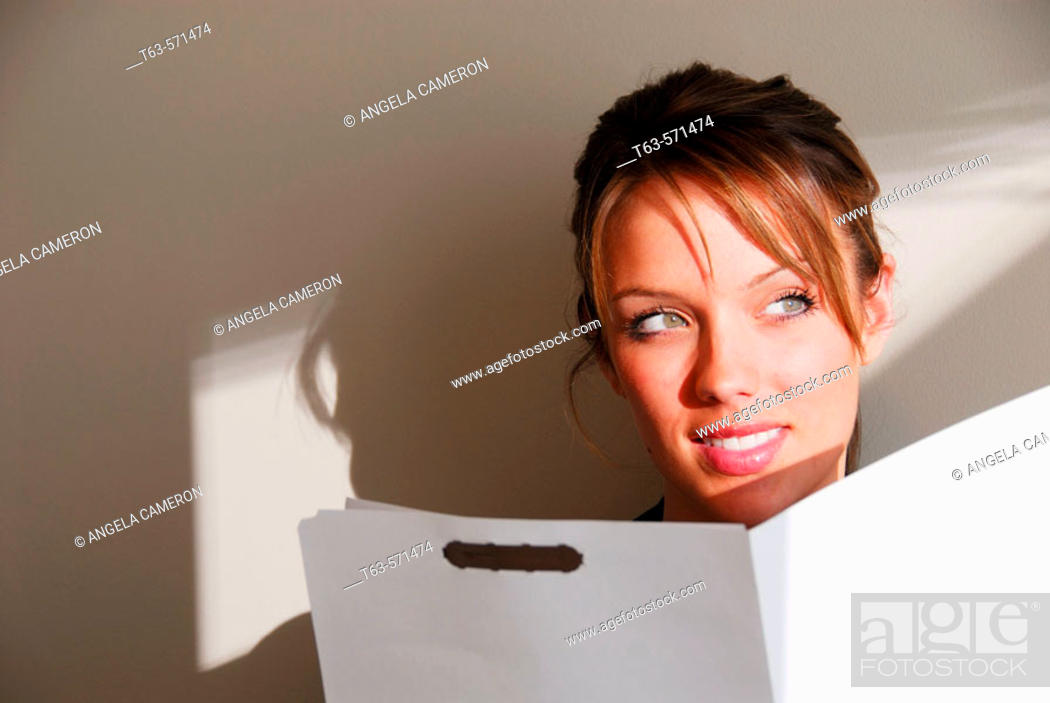 Stock Photo: 20 yr old young woman holding file folder.