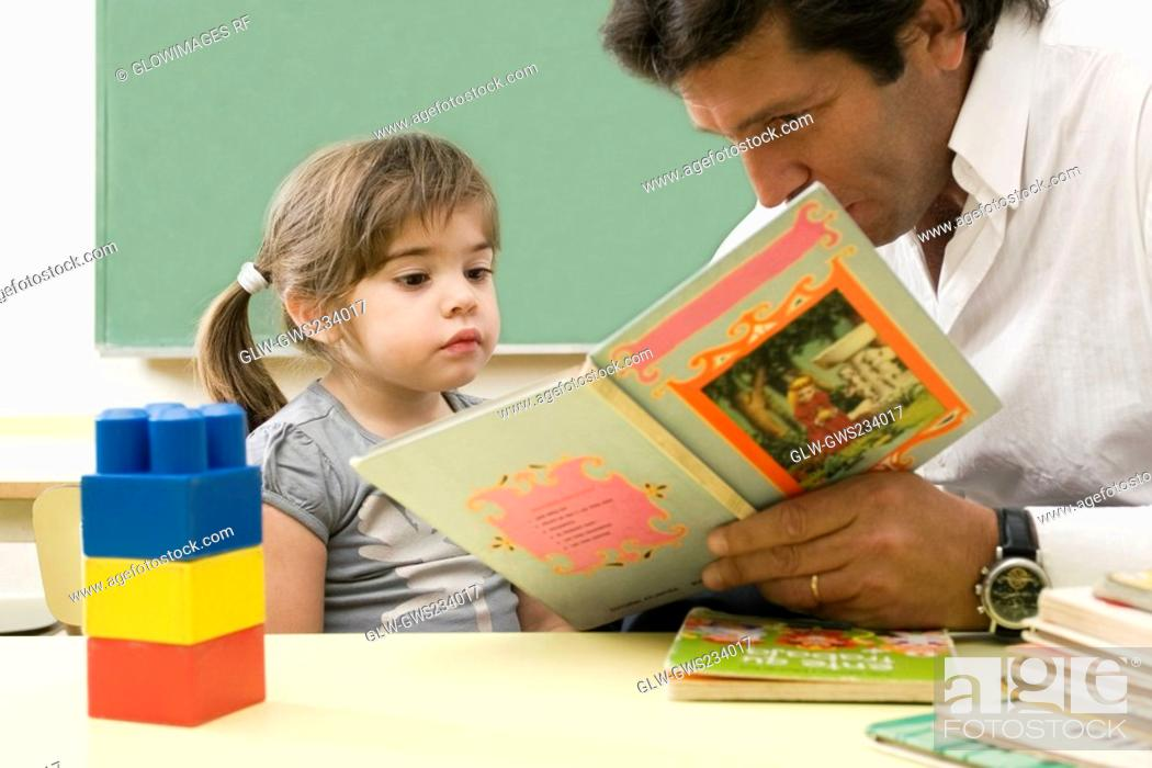 Stock Photo: Male teacher teaching his student in a classroom.