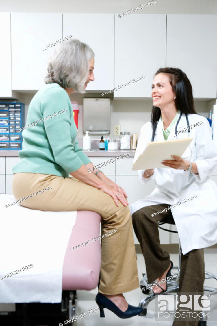 Stock Photo: Female doctor discussing file with senior female patient, smiling.