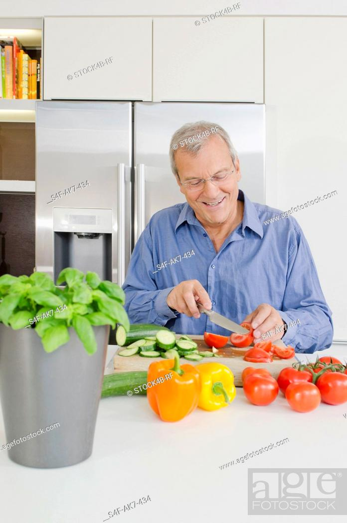 Stock Photo: Senor man slicing vegetables in kitchen.
