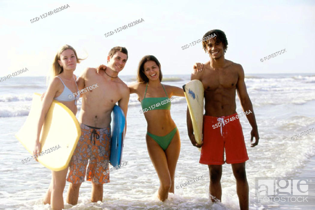 Stock Photo: Portrait of two teenage couples standing on the beach holding boogie boards.