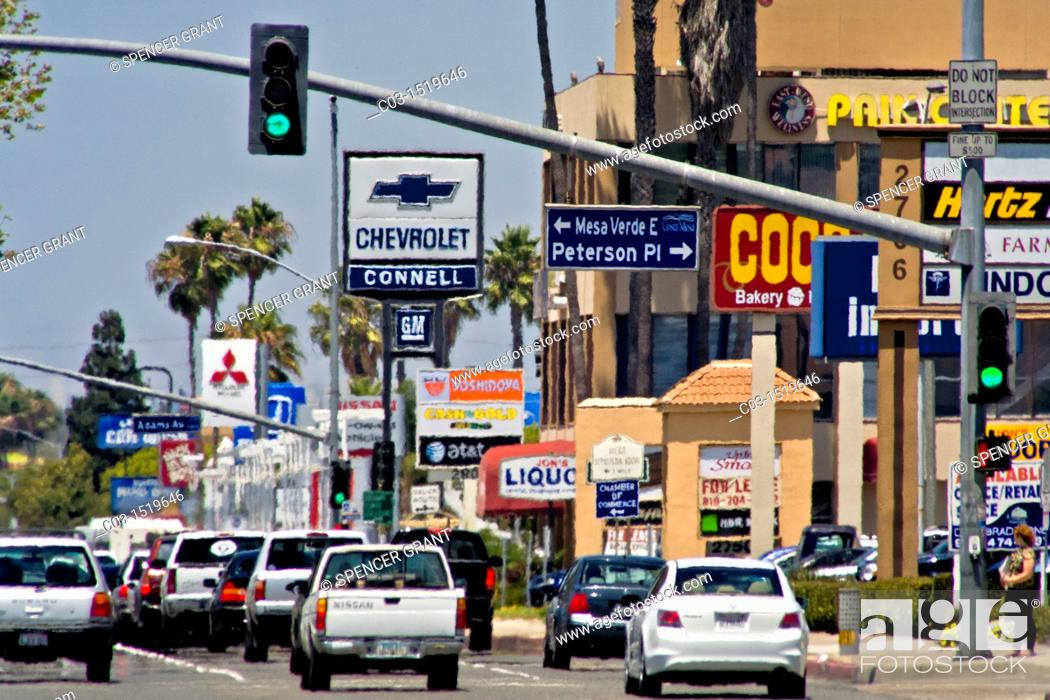 Stock Photo: Afternoon traffic passes retail advertising signs in Costa Mesa, CA  Note haze from summer heat.