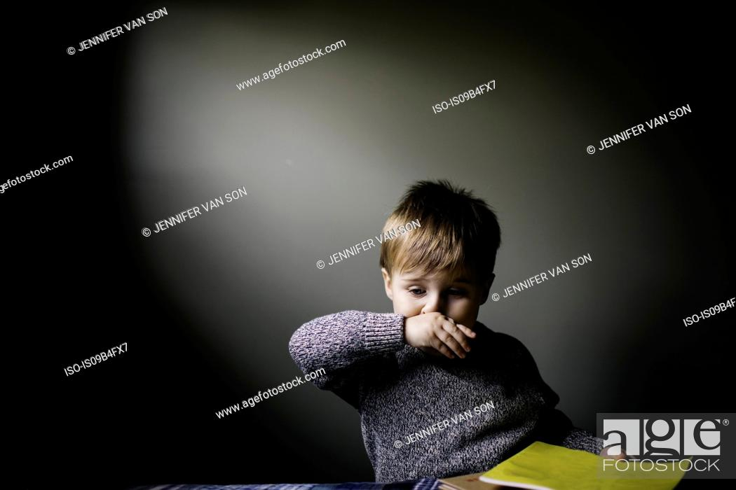 Stock Photo: Young boy wiping nose with hand.