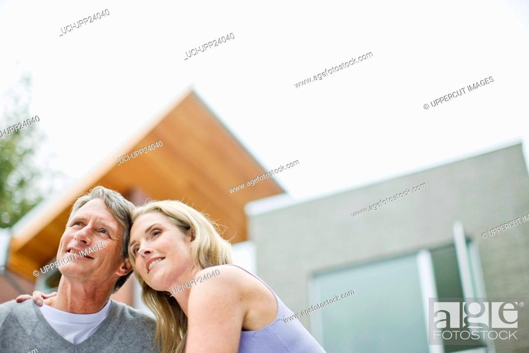 Stock Photo: Couple hugging on deck of modern house.