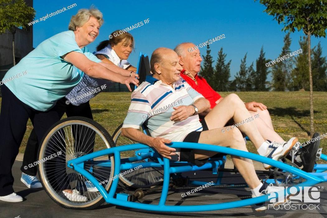Stock Photo: Two senior men sitting on a quadracycle and two senior women pushing it.