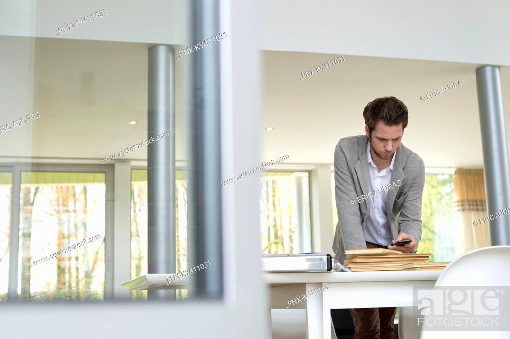 Stock Photo: Interior designer using a mobile phone in the office.