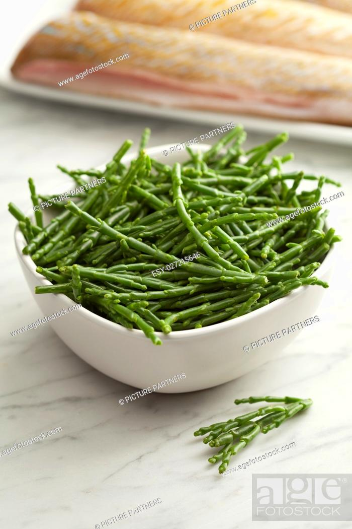 Stock Photo: Fresh raw green samphire in a bowl with fresh fish in the background.