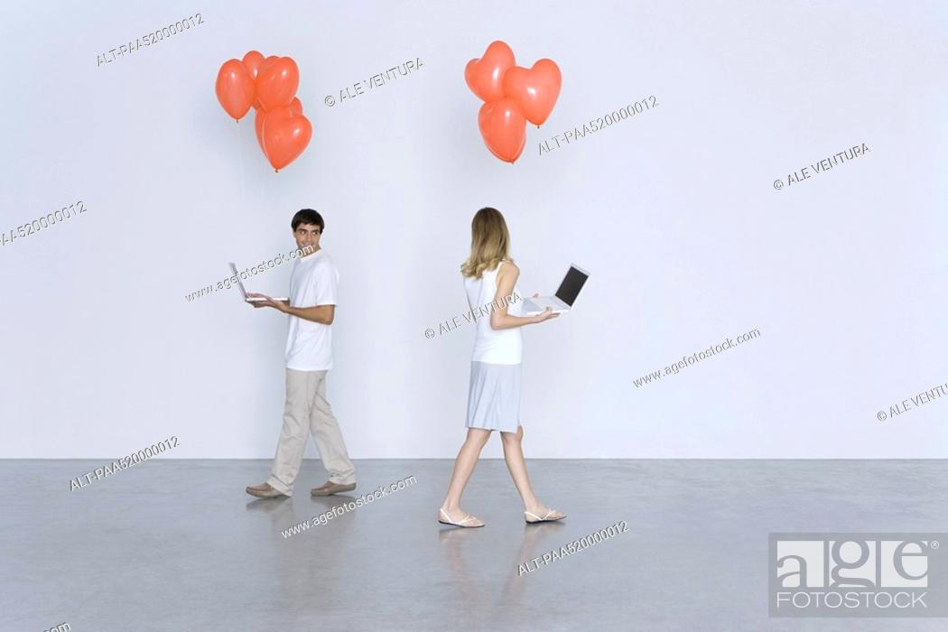 Stock Photo: Man and woman walking past each other, both carrying laptop computers and heart balloons.
