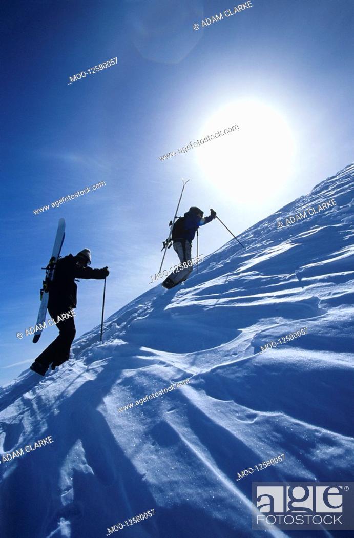 Stock Photo: Skiers hiking to mountain summit.