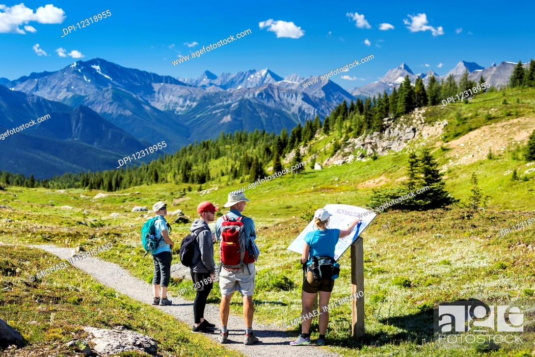 Stock Photo: A group of hikers viewing a interpretive sign along a meadow trail with mountain range in the distance and blue sky and clouds; Banff, Alberta, Canada.